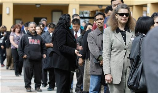 In this March 22, 2011 photo, job applicants wait in a long line at a job fair in San Jose, Calif. Fewer people applied for unemployment benefits last week, a sign that layoffs are dropping and companies may be stepping up hiring.(AP Photo/Paul Sakuma)