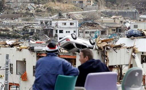 Evacuees chat at each other near the debris at the March 11 earthquake and tsunami-destroyed town of Onagawa, Miyagi prefecture, northeastern Japan, Thursday, March 31, 2011. (AP Photo/Lee Jin-man)