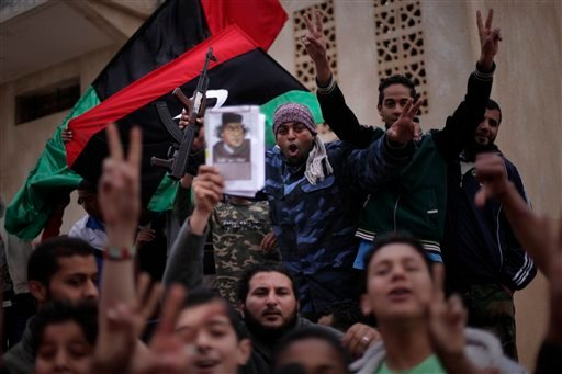 An armed Libyan rebel and other people shout slogans during a demonstration in Benghazi, Libya, Wednesday, March 30, 2011.