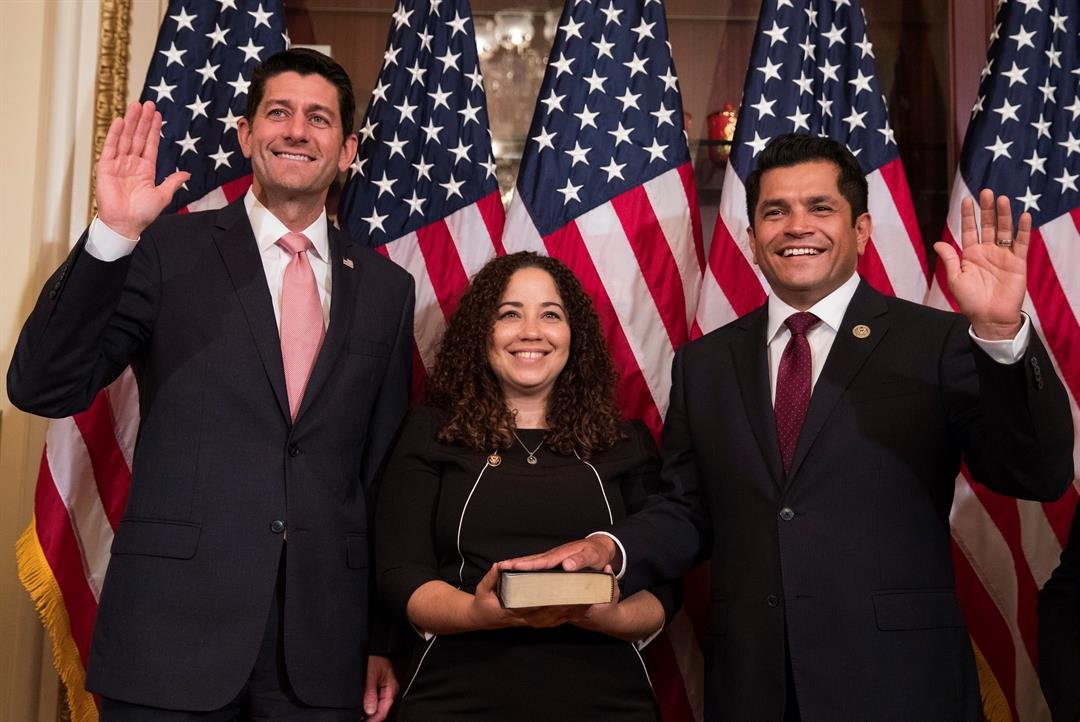 Speaker of the House Paul Ryan, R-Wis., left, Representative-elect Jimmy Gomez, D-Calif., right, and Mary Hodge, Gomez's wife holding the Bible participate in a ceremonial swearing-in on Capitol Hill in Washington, Tuesday, July 11, 2017. (AP Photo/Caroly