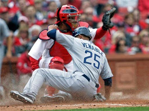 San Diego Padres' Will Venable (25) scores from third on a sacrifice fly by teammate Orlando Hudson as St. Louis Cardinals catcher Yadier Molina (4) waits for a throw during the fourth inning of a baseball game on opening day Thursday, March 31, 2011.