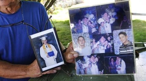 In this Monday, July 10, 2017 photo, Clifford Kang, father of soldier Ikaika E. Kang, poses with photo of his son in Kailua, Hawaii.