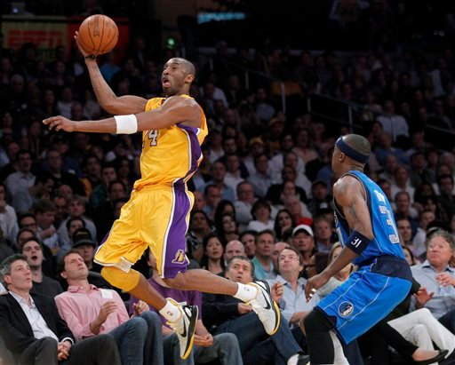 Los Angeles Lakers guard Kobe Bryant, left, passes the ball as Dallas Mavericks guard Rodrigue Beaubois watches during the first half of an NBA basketball game in Los Angeles, Thursday, March 31, 2011.