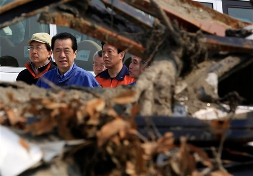Japanese Prime Minister Naoto Kan, center, walks past the rubble in front of municipal building Saturday, April 2, 2011 in Rikuzentakata, Iwate Prefecture, northern Japan. (AP Photo/Eugene Hoshiko)