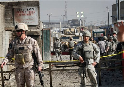 U.S. soldiers stand guard in front the gate of a U.S. base after an attack in Kabul, Afghanistan, on Saturday, April 2, 2011. (AP Photo/Musadeq Sadeq)