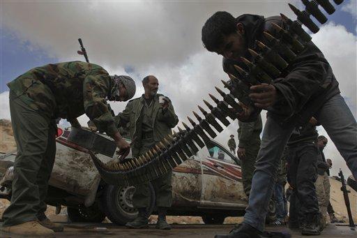 Libyan rebels clean machine gun ammunition with petrol before heading for the front line near Brega, Libya, Saturday, April 2, 2011. (AP Photo/Altaf Qadri)