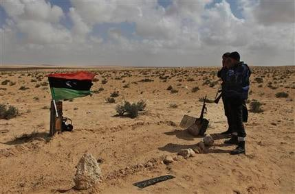 Libyan rebels pray near the a graves of their fellow rebels who were allegedly killed in NATO coalition airstrike overnight at the frontline, near Brega, Libya, Saturday, April 2, 2011. (AP Photo/Altaf Qadri)