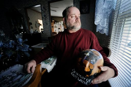 In this March 8, 2011 photo, Gary Quarles holds a helmet made in memory of his son Gary Wayne Quarles at his home in Naoma, W.Va. (AP Photo/Jeff Gentner)