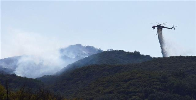 In this photo provided by the Santa Barbara County Fire Department, a Skycrane makes a water drop on hot spots near Hot Spring Canyon and Highway 154 in the Whittier fire area near Santa Barbara, Calif., Wednesday, July 12, 2017.