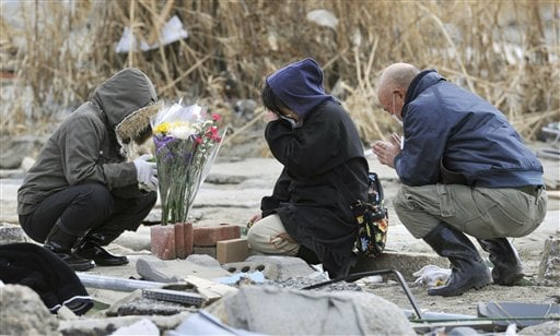 A woman, center, prays at her missing parents' house devastated by a tsunami in Rikuzentakata, northern Japan Monday, April 4, 2011. (AP Photo/Kyodo News)