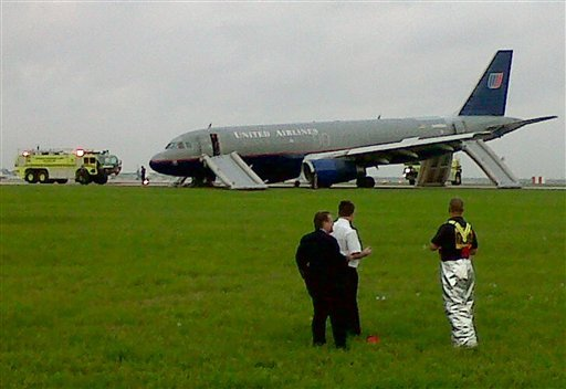 In this image made with a cell phone, a United Airlines plane sits on a runway after making an emergency landing shortly after takeoff at Louis Armstrong New Orleans International Airport.