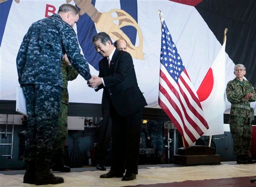Japan's Defense Minister Toshimi Kitazawa, center, shakes hands with Adm. Patrick M. Walsh, Commander of U.S. Pacific Fleet, during a ceremony in the aircraft carrier USS Ronald Reagan (CVN76) Monday, April 4, 2011.