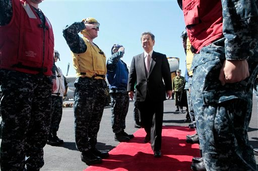 Japan's Defense Minister Toshimi Kitazawa is greeted upon his arrival on the deck of the aircraft carrier USS Ronald Reagan (CVN76).