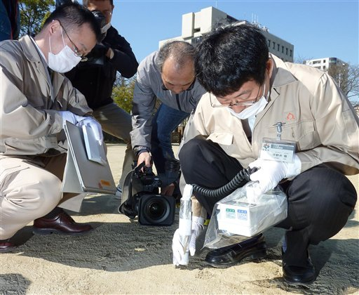 Prefectural government's employees monitor amount of radiation on the ground of an elementary school in Fukushima, northern Japan Tuesday, April 5, 2011. (AP Photo/Kyodo News)