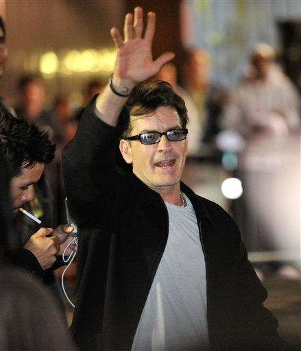 "Charlie Sheen waves to fans as he leaves the Chicago Theatre, Sunday, April 3, 2011, in Chicago. Promising ""the real story,"" the 45-year-old former ""Two and a Half Men"" star continued his month-long, 20-city variety show tour."