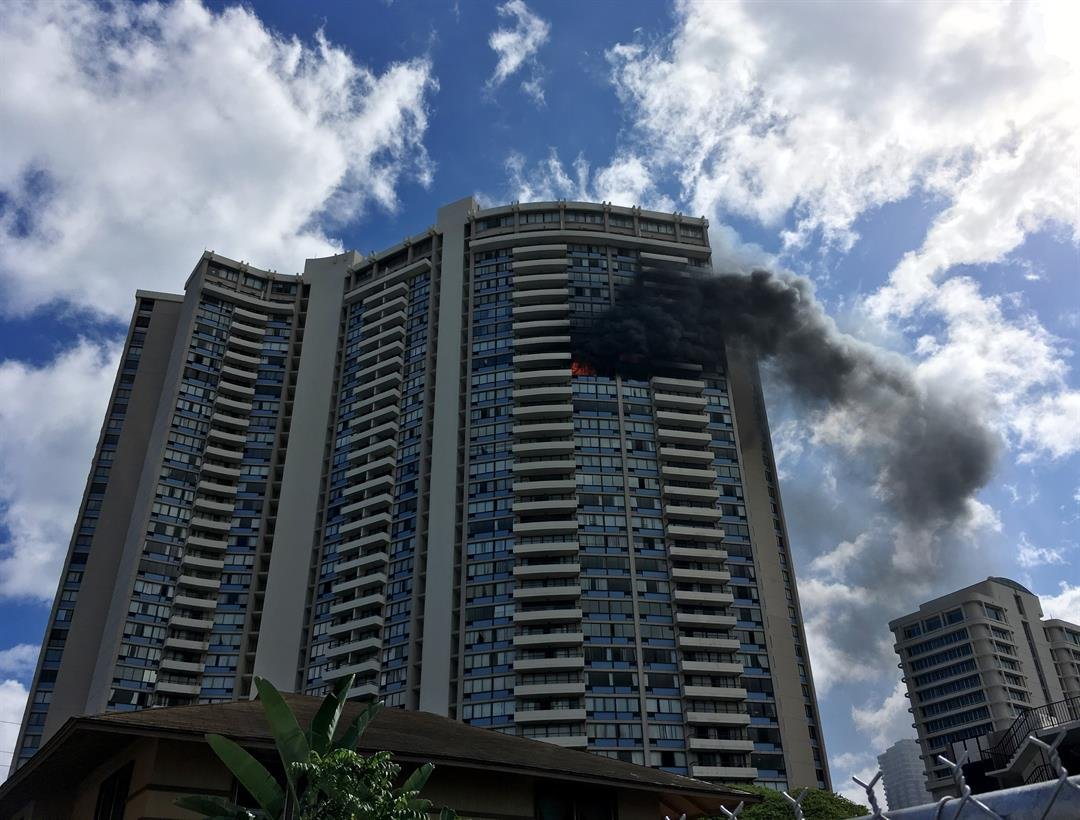 Smoke billows from a high-rise apartment building in Honolulu, Friday, July 14, 2017. (AP Photo/Audrey McAvoy)