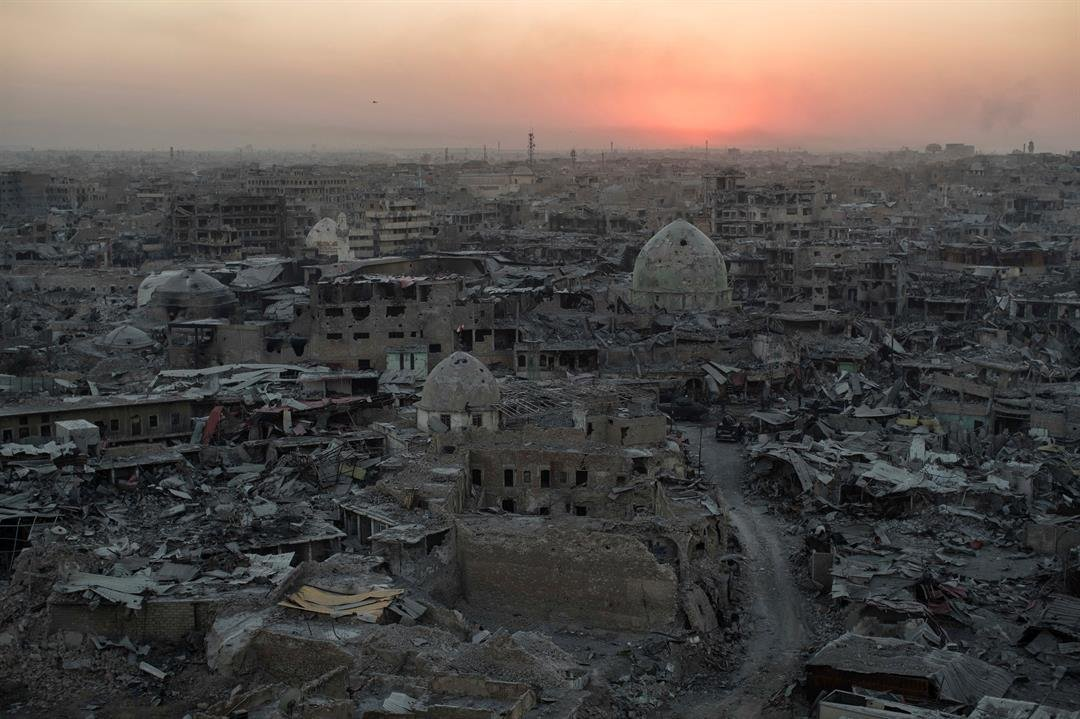 The sun sets behind destroyed buildings in the west side of Mosul, Iraq on Tuesday, July 11, 2017. (AP Photo/Felipe Dana)