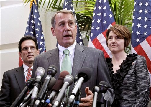 House Speaker John Boehner of Ohio, center, flanked by House Majority Leader Eric Cantor of Va., left, and Rep. Cathy McMorris Rodgers, R-Wash., talks to reporters on Capitol Hill in Washington, Wednesday, April 6, 2011.