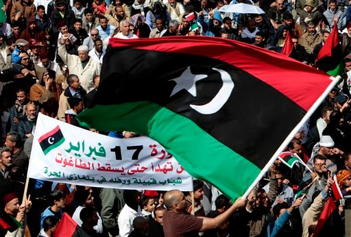 Anti-Libyan leader Moammar Gadhafi protesters, wave the pre-Gadhafi Libyan flag during a protest after Friday prayers at Court Square, in Benghazi, eastern Libya, Friday March 11, 2011. (AP Photo/Hussein Malla)