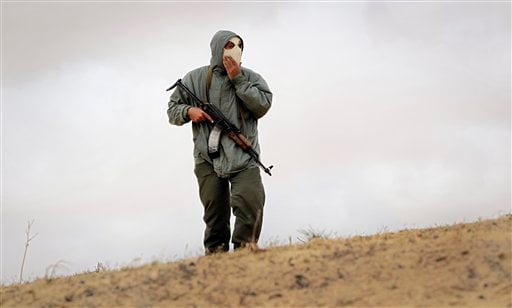 A Libyan rebel fighter monitors the skyline on top of a sand dune, near Brega, Libya Wednesday, April 6, 2011.