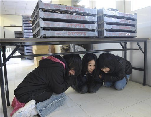 Children hide under a table at a junior high school as a strong aftershock jolted the area at Ishinomaki, northeastern Japan March 24, 2011, following the March 11 earthquake and resulting tsunami. (AP Photo/The Yomiuri Shimbun, Miho Takahashi)