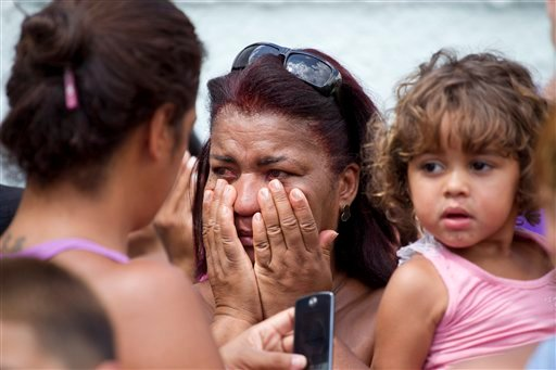 A woman reacts outside a school after a shooting at the school in Rio de Janeiro April 7, 2011. Brazilian authorities say that a gunman opened fire in an elementary school and at least 13 people are dead, including the gunman. (AP Photo/Victor R. Caivano)