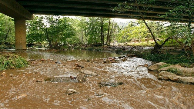 Muddy floodwaters of the East Verde River flow under a bridge where one victim of the flash flood was found.