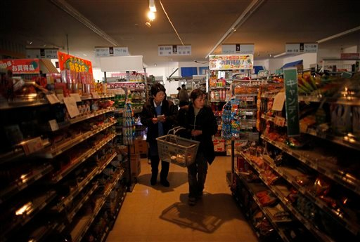 Japanese people buy food at a supermarket with no electricity in Ishinomaki, Miyagi Prefecture, northern Japan Friday, April 8, 2011. (AP Photo/Vincent Yu)