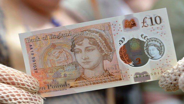 People in period costume display the new £10 note featuring Jane Austen, which marks the 200th anniversary of Austen's death.