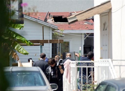 A large hole is left in the roof of a home after police and firefighters removed a device from the roof of a home next to the Chabad House Lubavitch in Santa Monica, Calif.