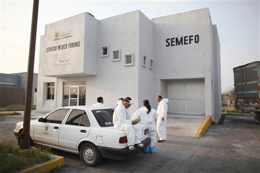 Morgue employees take a break outside the local morgue where the bodies of 59 people found in a mass grave on Wednesday are being held, in Matamoros, northern Mexico, Thursday, April 7, 2011.
