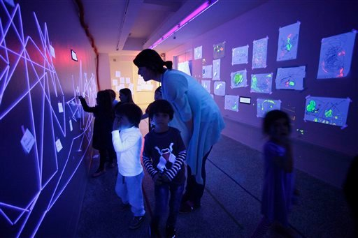 In this March 31, 2011 photo, a teacher leads her students in a discussion of artwork illuminated by ultraviolet lamps in a hallway of the Blue School, in New York. (AP Photo/Mark Lennihan)