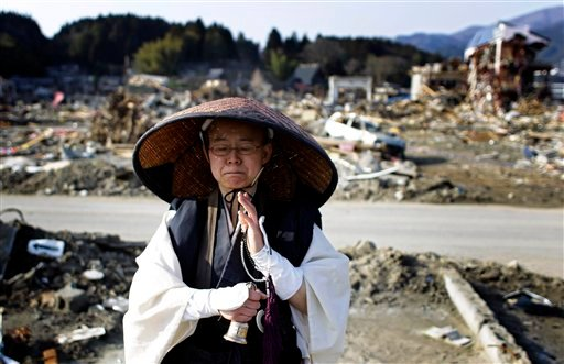 A Japanese Buddhist monk prays at an area devastated by the March 11 earthquake and tsunami in Rikuzentakata, Iwate Prefecture, Japan, Sunday, April 10, 2011.