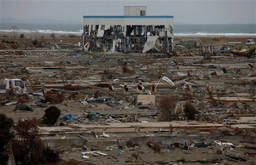 Buddhist monks pray in an area destroyed by tsunami in Natori, Miyagi Prefecture, northern Japan, Monday, April 11, 2011, one month to the day after an earthquake and tsunami devastated the city. (AP Photo/Vincent Yu)