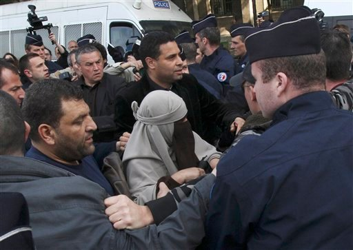 An unidentified veiled woman is taken away by plain clothed and uniformed police officers, flanked by a friend, center right, in Paris Monday, April 11, 2011. (AP Photo/Michel Euler)