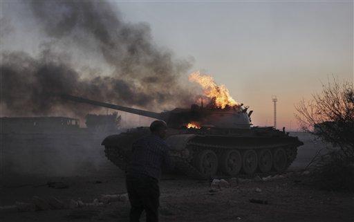 A cameraman films a pro-Gadhafi forces tank as it burns on the outskirts of Ajdabiya, in Libya Sunday, April 10, 2011. (AP Photo/Altaf Qadri)
