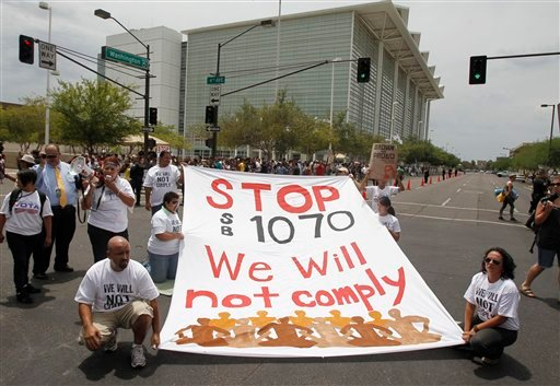 FILE - In this July 22, 201 photo, protesters block the street to protest the SB1070 Arizona immigration law in front of U.S. District Court in Phoenix.