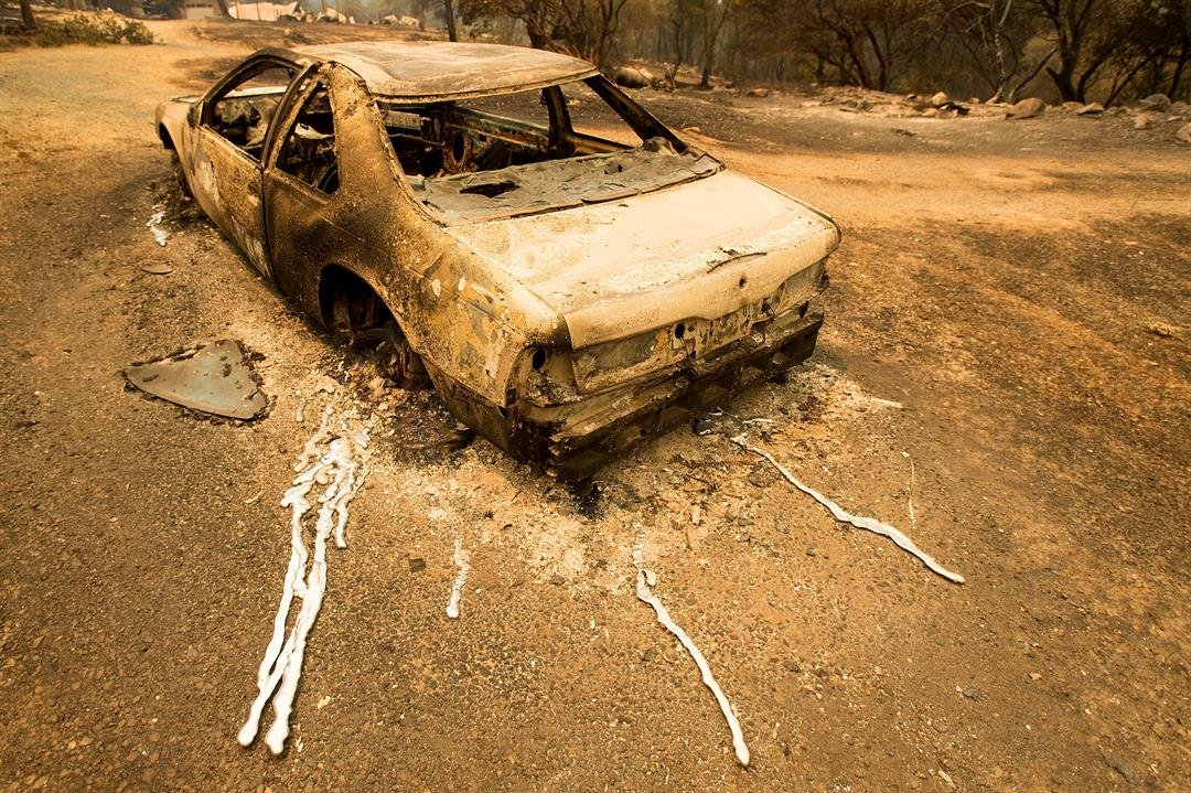 A scorched car rests next to a residence leveled by the Detwiler fire near Mariposa, Calif., on Wednesday, July 19, 2017. (AP Photo/Noah Berger)