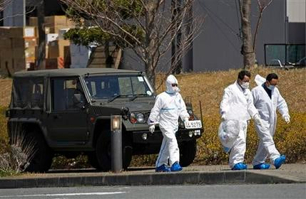 People in radiation protect suits walk in J-Village in Naraha, Fukushima Prefecture, northeastern Japan Tuesday, April 12, 2011.  (AP Photo/Hiro Komae)