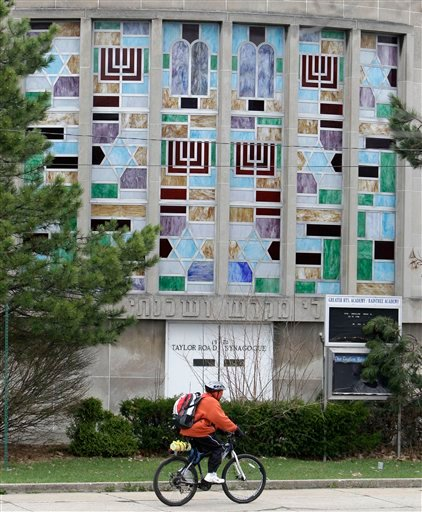 A man rides his bicycle past the Taylor Road Synagogue, Tuesday, April 12, 2011, in Cleveland Heights, Ohio.