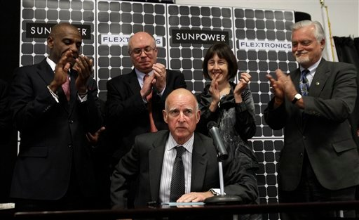 alifornia Gov. Jerry Brown draws applause after signing Senate Bill 2X, as officials including California Senator Joseph Simitian (D-Palo Alto) (center, behind Brown), the author of the bill, look on at Flextronics in Milpitas, Calif.