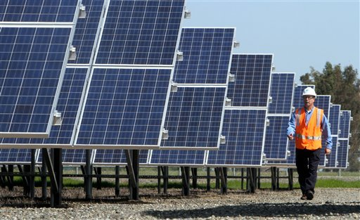 Greg Bosscawen, manager of renewable energy for Pacific Gas and Electric Co., walks past solar panels at PG&E's Vaca-Dixon solar energy site near Vacaville, Calif., Tuesday, April 12, 2011.