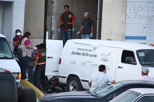 Forensic workers transfer bodies from a van into a large truck in the northern border city of Matamoros, Mexico Wednesday April, 6, 2011.
