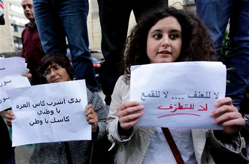 "Pro-reform in Syria activists, hold Arabic placard: ""No to violence, no to oppression and no to fanaticism, right, and I want to drink the drink glory my nations, cheers my nation, left."" (AP Photo/Hussein Malla)"