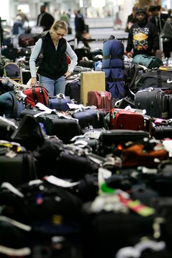 In this Feb. 20, 2007 file photo, Carolann Manfredi, of Princeton, N.J., searches through luggage for a bag she says has been missing for five days, at the Philadelphia International Airport.