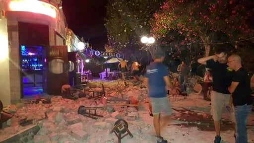People walk near a damaged building after an strong earthquake on the Greek island of Kos early Friday, July 21, 2017. (Kalymnos-news.gr via AP)