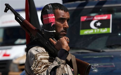 A Libyan rebel carrying an AK-47 guards at the western gate of Ajdabiya, Libya Wednesday, April 13, 2011.