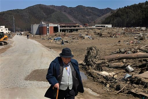 In this April 5, 2011 photo, a man walks past Okawa Elementary School devastated by the March 11 earthquake and tsunami, in Ishinomaki, Miyagi Prefecture, northern Japan.
