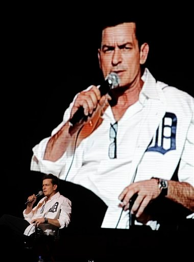 An image of Charlie Sheen is projected in the background as he performs at the Fox Theatre in Detroit, Saturday, April 2, 2011.