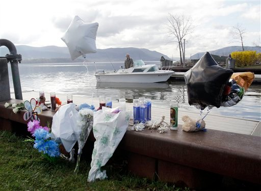 A fisherman is seen behind an informal memorial at the boat ramp where Lashanda Armstrong drove her minivan into the Hudson River on Tuesday night killing herself and three of her children, in Newburgh, N.Y., on Thursday, April 14, 2011.
